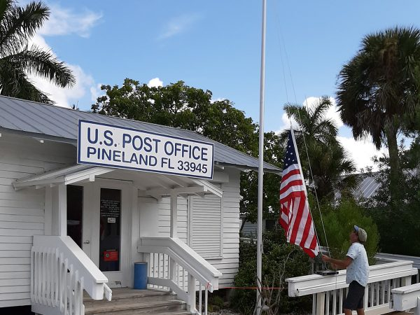 Andy Jendrusiak, RRC Groundskeeper, raises the flag outside the Pineland Post Office.