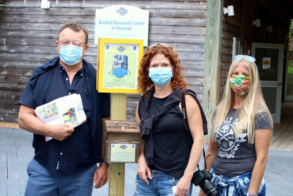 three people wearing masks standing outside of the Randell Research Center