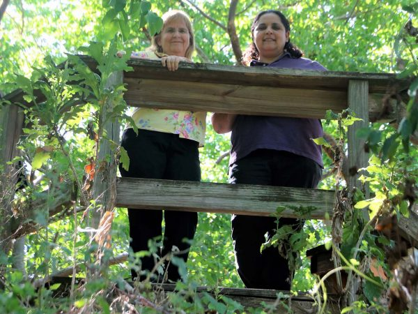 two women stand at a wooden fence.