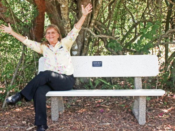 """Cindy Bear sitting on a bench smiling with her arms raised. A plaque in the bench reads """"Cindy Bear with Love and Respect from your RRC Family."""