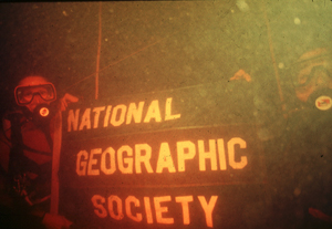 divers holding a National Geographic Society banner underwater