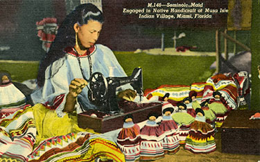 Figure 1: Post card of woman making dolls (2013-6-24). Donated by Anne Reynolds.