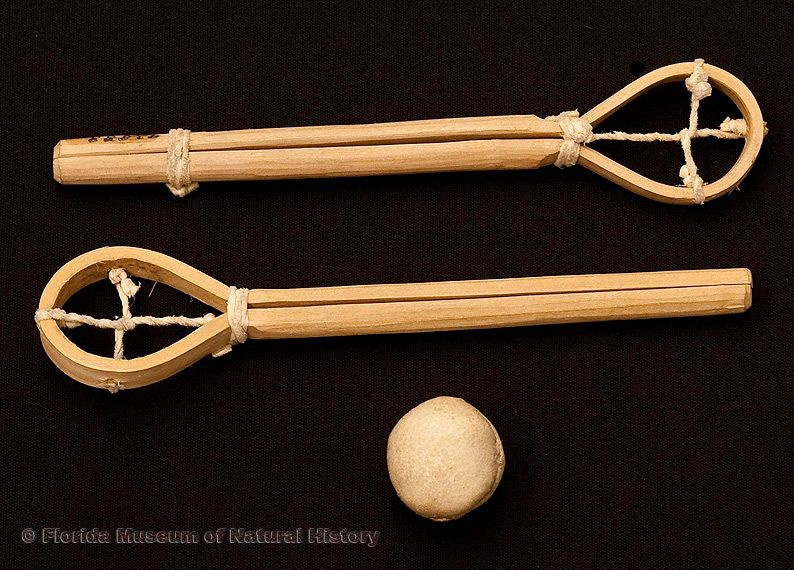 "Miniature stickball racquets (pair) and ball, Seminole, cypress wood and buckskin, collected 1950 from William McKinley Osceola's camp, sticks 6.9"" long, ball 1.2"" diameter (92888, 92887)."