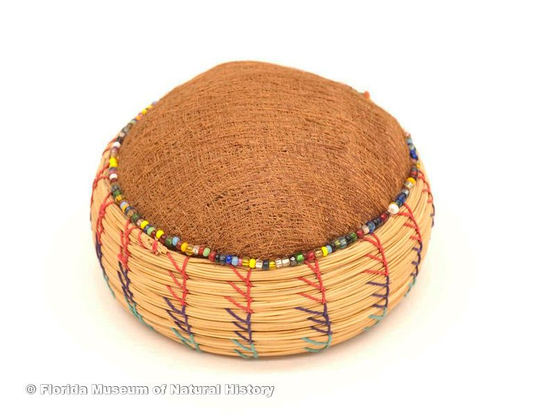 "Basket pincushion, Seminole, sweetgrass, cotton thread, palmetto fiber, late 20th century, 3.9"" diameter (87-46-6)."