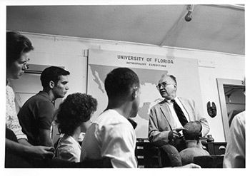 Figure 6: John M. Goggin with anthropology students in University of Florida classroom, examining pottery, circa 1961. Photograph by Flip Schulke, courtesy of the George A. Smathers Library Digital Collections.