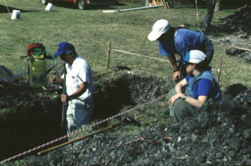 From left to right, Howard Yamataki takes a soil sample from the base of Trench 9c at the Pineland site as Karen Walker and Maxine Levin look on, 1992.
