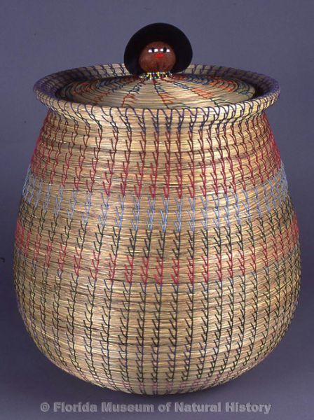 "Basket, Seminole, sweetgrass, cotton thread, palmetto fiber, cotton cloth, glass beads, 1990s; made by Agnes Billie Cypress (basket) and Lucy Johns (lid), Immokalee, 20.0"" high (97-8-1)."