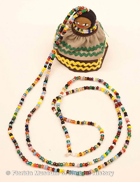"Doll, female, necklace, Seminole, cotton cloth, glass beads, palm fiber, ca. 2000, doll is 2.5"" high (2006-20-8)."