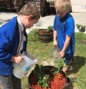 two kids water plants