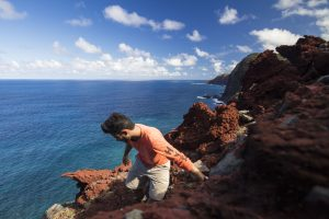 Researcher Chris Johns travels along the cliffs of Molokai in Hawaii in search of the host plant for the Philodoria marginestrigata moth. Florida Museum of Natural History photo by Chris Johns