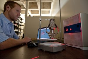 Florida Museum research associate Aaron Wood demonstrates a 3-D scanner in the museum's vertebrate paleontology collections. Florida Museum of Natural History photo by Kristen Grace