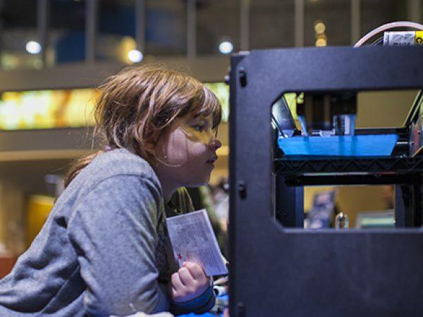 Girl looking at 3D printer.