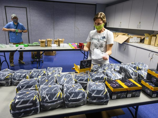 people in masks packing supplies