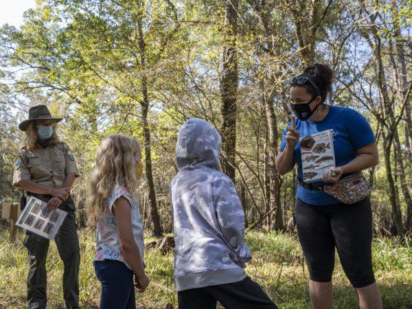Children, teacher and park ranger standing in the woods