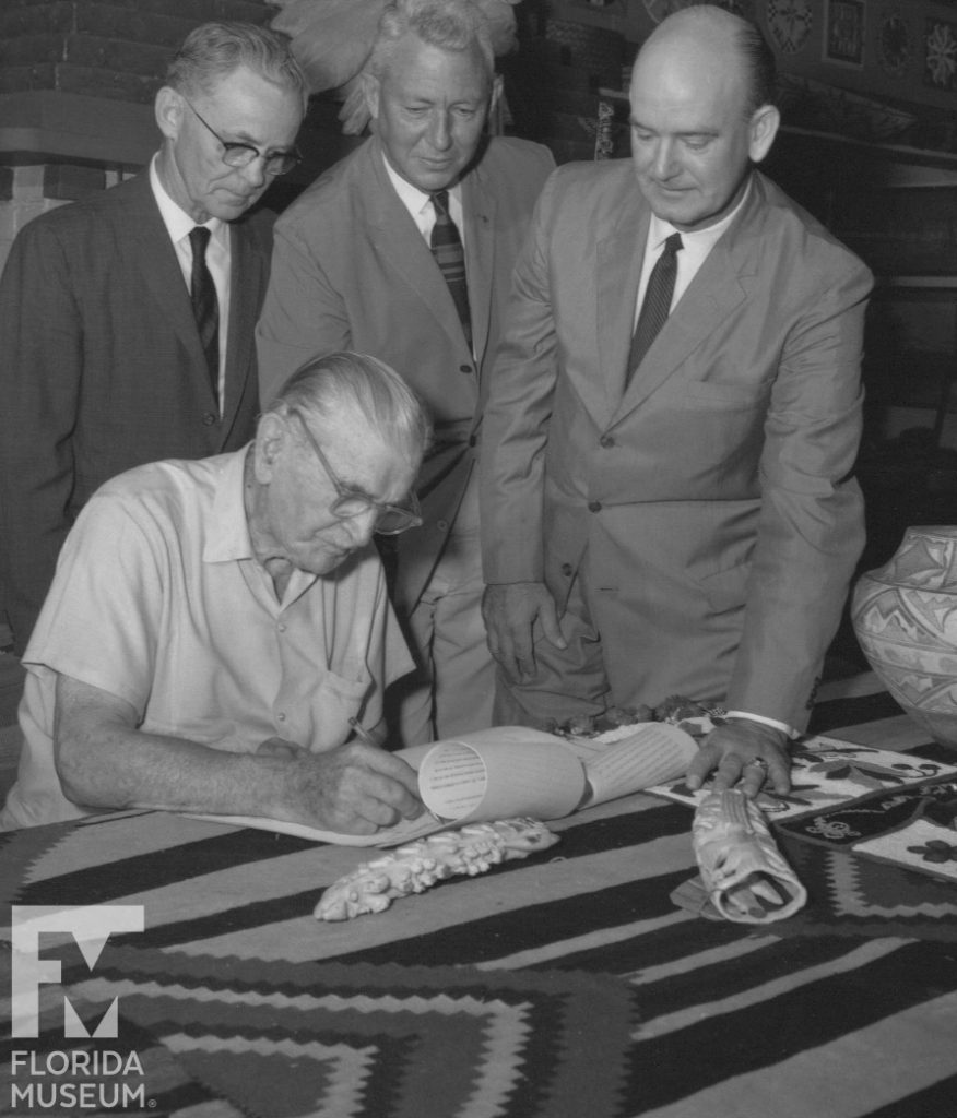 four men signing document
