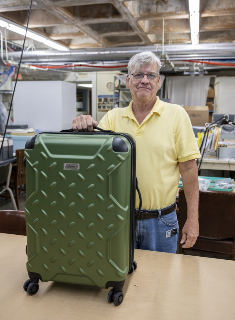 researcher holds a large suitcase full of teaching materials