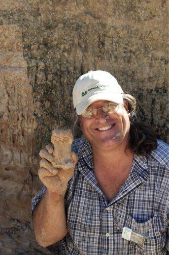 man at fossil dig holding up large square fossil bone