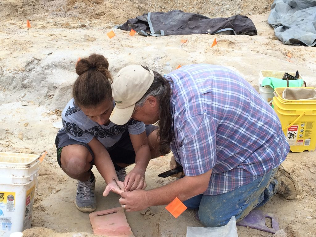 researcher and student looking closely at a fossil at a dig site