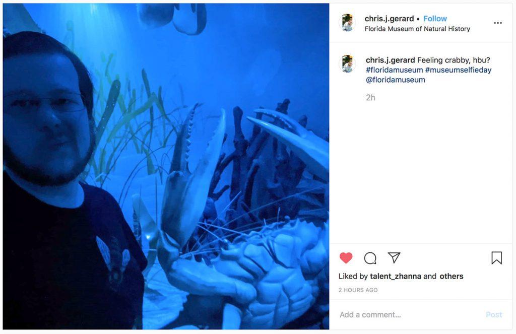 man taking selfie in very dark and blue museum exhibit space