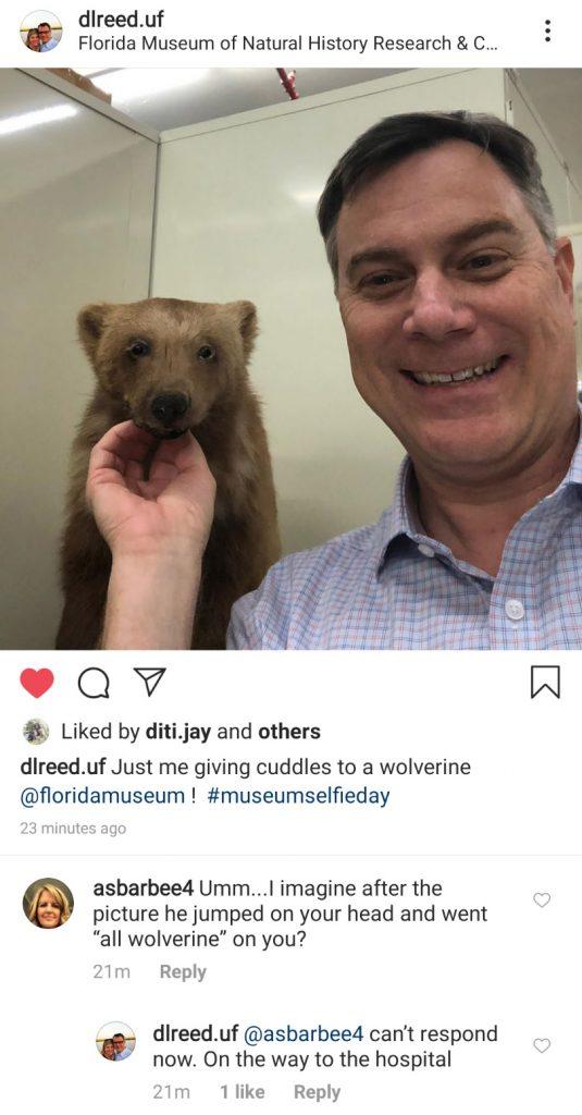man taking selfie in front of taxedermied wolverine