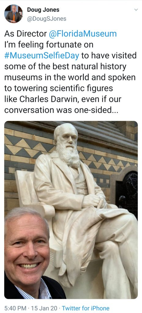 man taking selfie in front of Charles Darwin statue