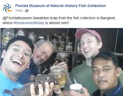 group holding fish specimens