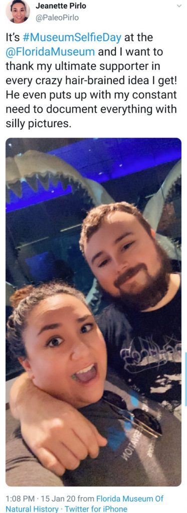 woman and man in a selfie in front of megalodon jaw