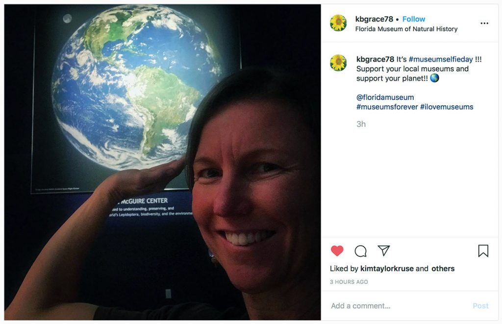 woman taking selfie in front of large earth image