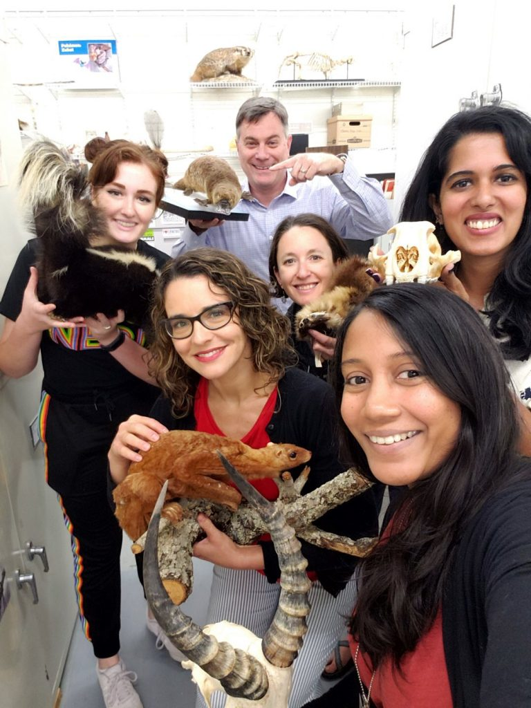 group of scientists holding mammal specimens