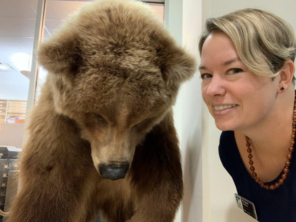 woman in selfie with taxedermied bear