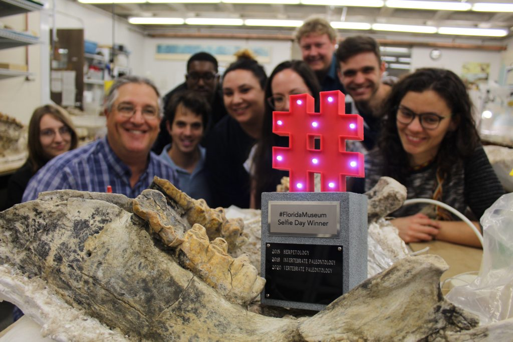 hashtag trophy sitting on a fossil surrounded by researchers and students