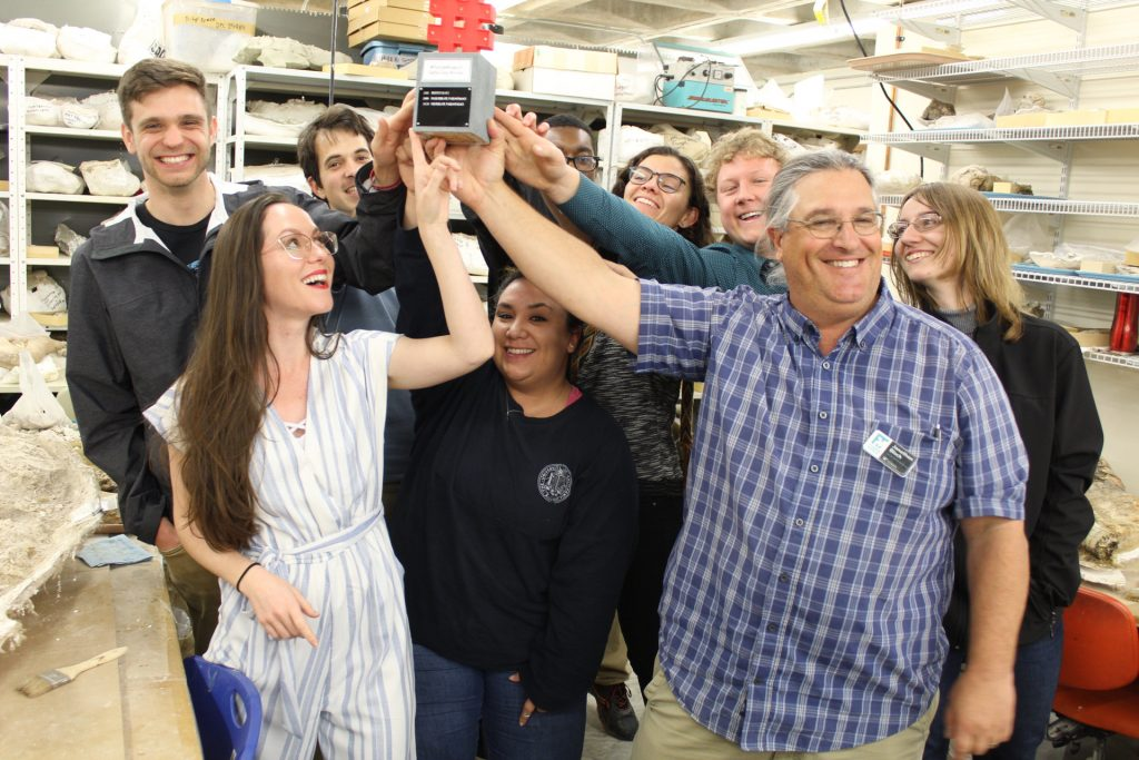paleontology students reaching up to tough a trophy