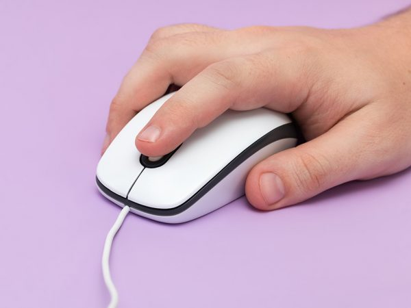 a hand holding a older style mouse with a cord