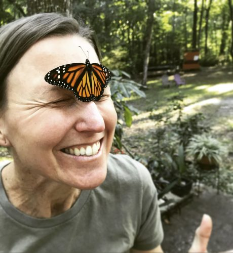A woman has a monarch butterfly on her face.