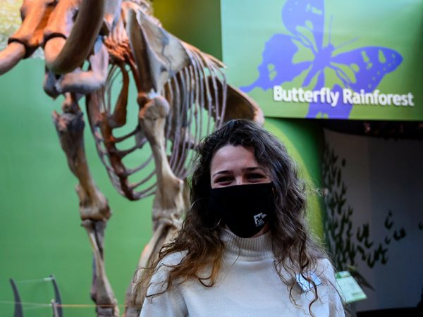 woman in mask standing in front of mammoth skeleton