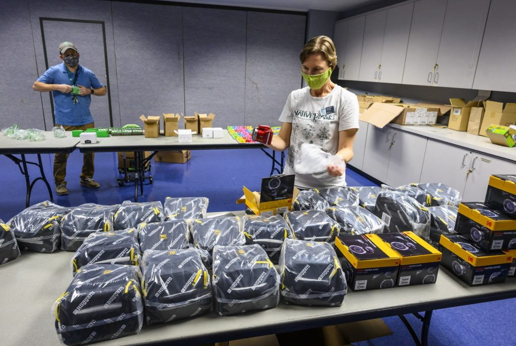 This image shows two people unwrapping cameras in a classroom at the Florida Museum.