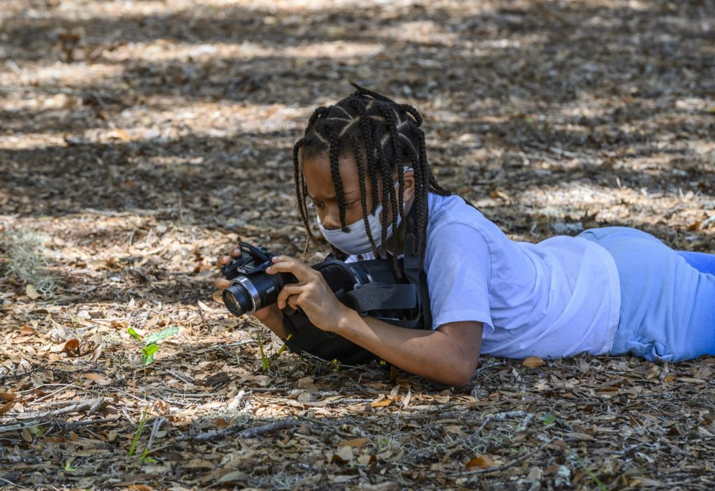 A photo camp student laying on the ground to photograph a plant.