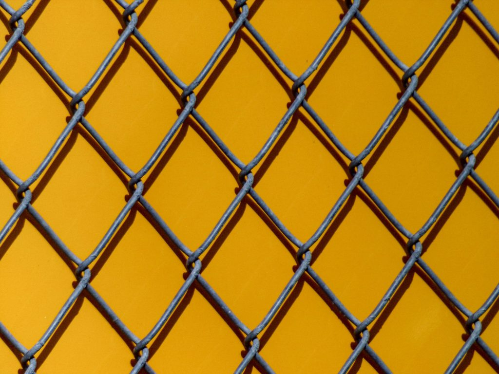 A photo of a chain link fence agents a yellow wall.