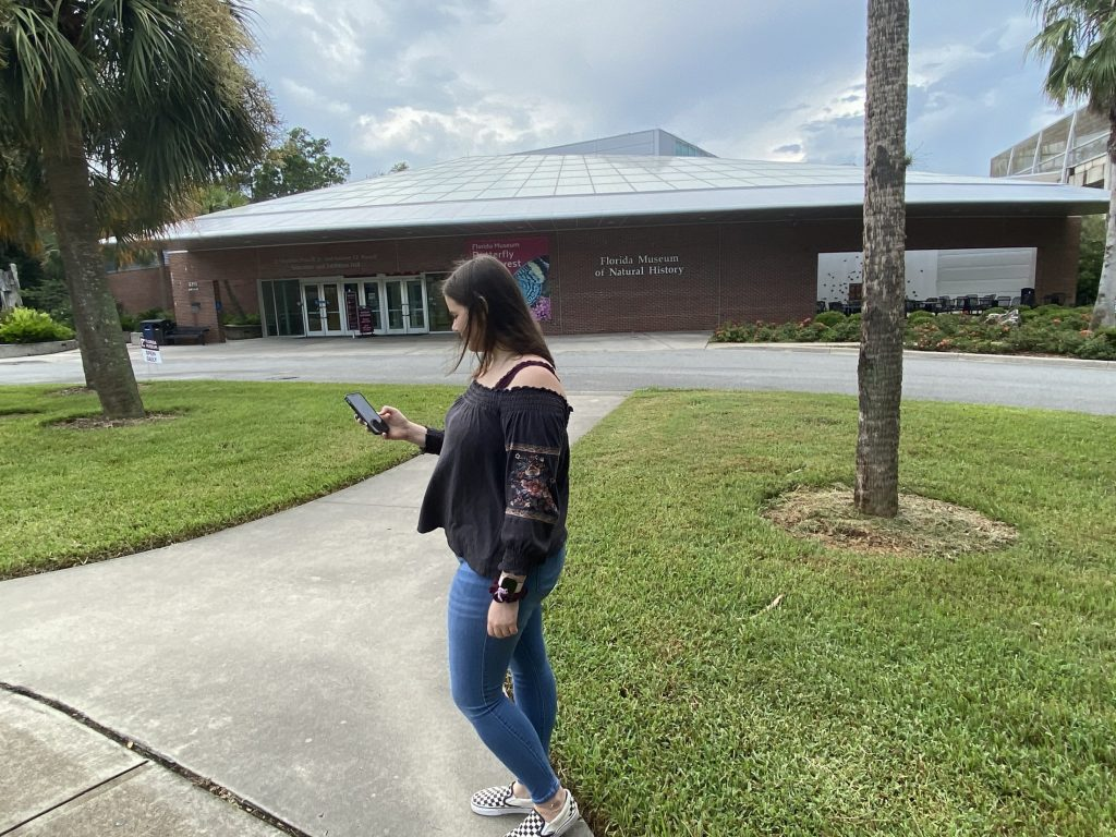 Person looking at phone, the Florida Museum can be seen behind her