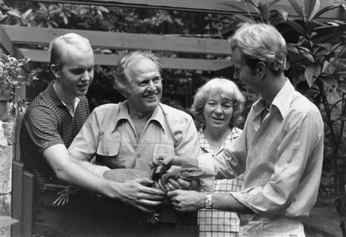 vintage black and white photo of a family holding a large lizard-like animal