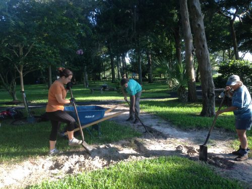 people shoveling dirt into wheelbarrow
