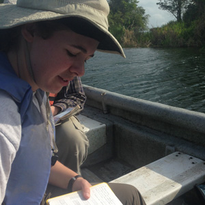 Sophie Westacott writing in her field notebook on Lake Bayano. Photo by S. Sanchez.