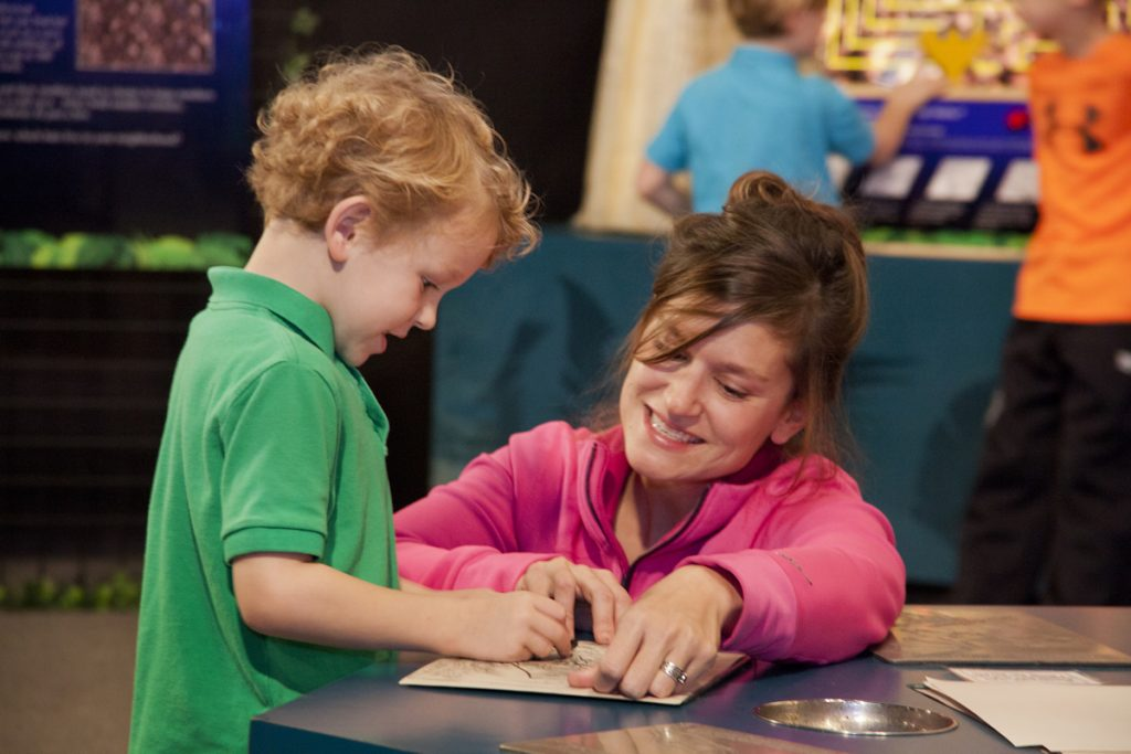 child and parent making crayon rubbing