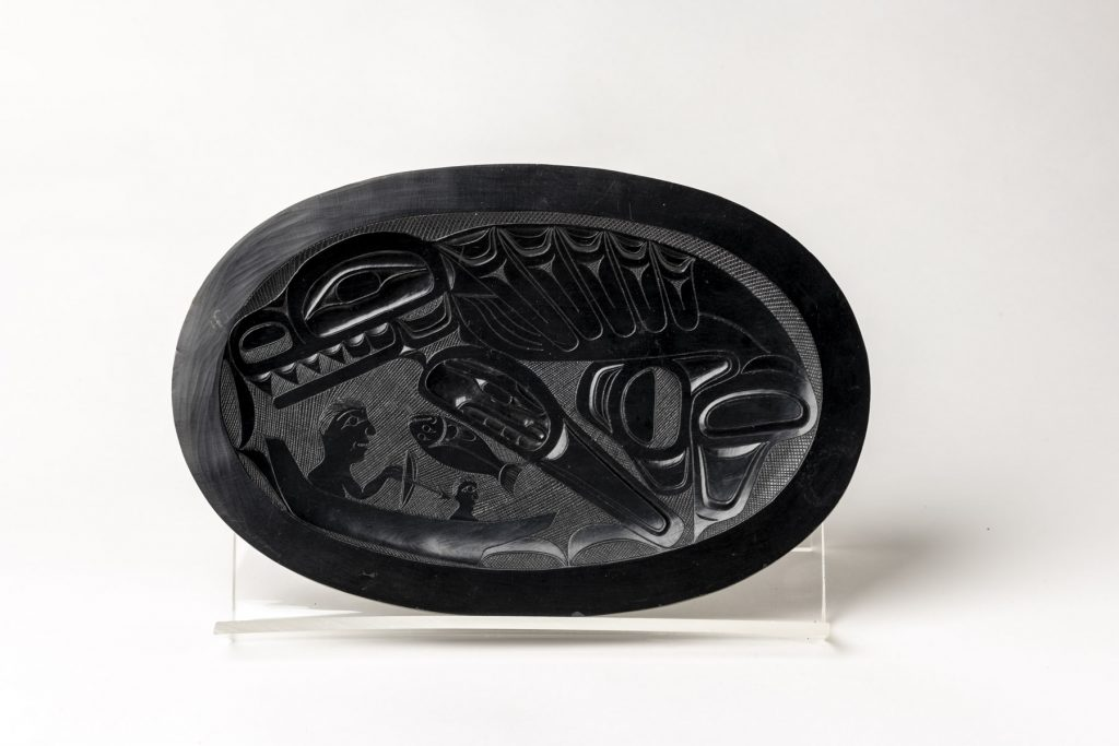 This shallow argillite platter depicts a killer whale, two men in a boat and a fish in its basin. ©Florida Museum photo by Kristen Grace
