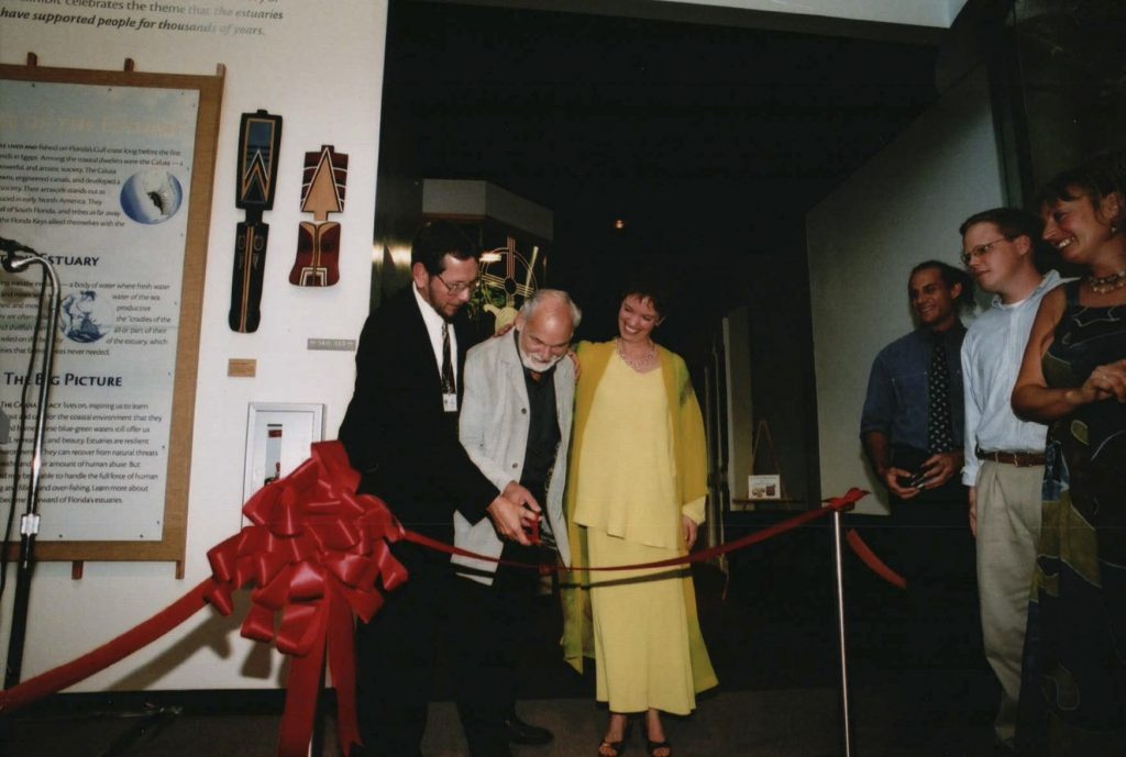 three peple cut ceremonial ribbon