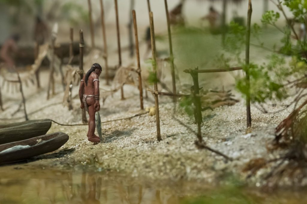 diorama close up of person carrying fish from a boat