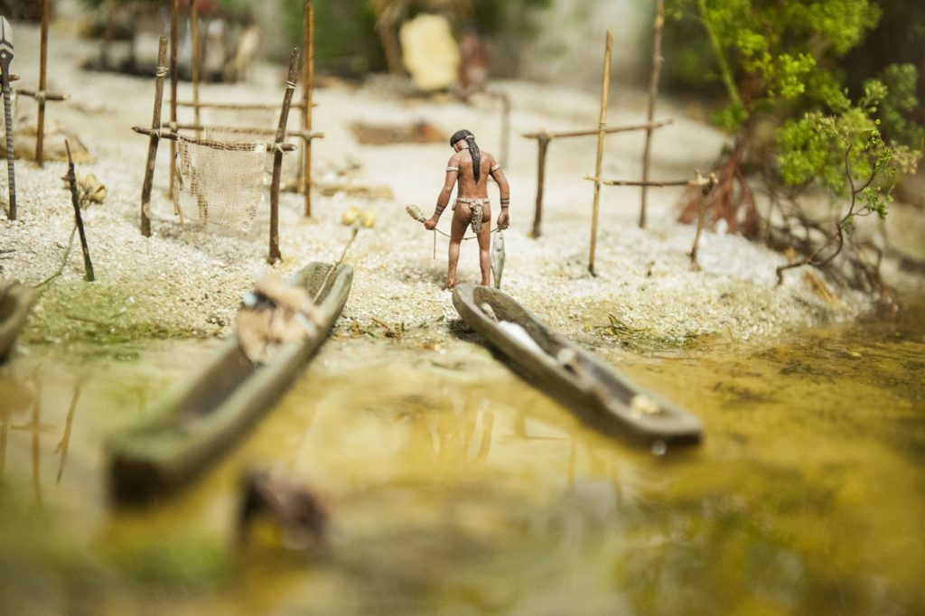 diorama showing native fisher returning from the water