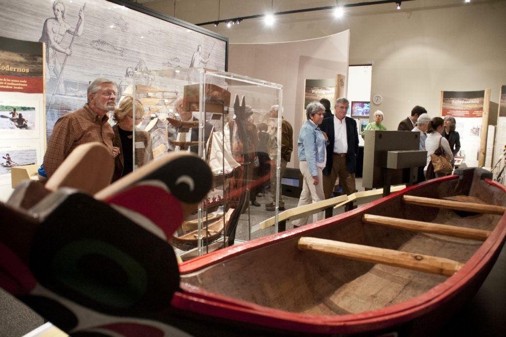 visitors looking at large wooden canoe