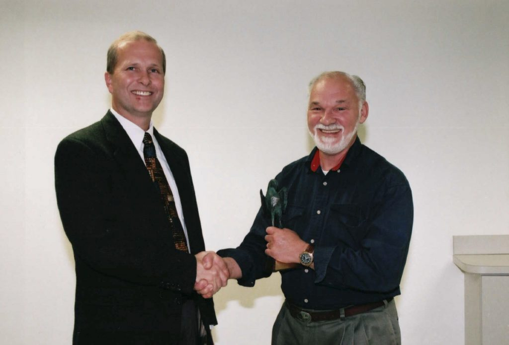 two men shaking hands over award