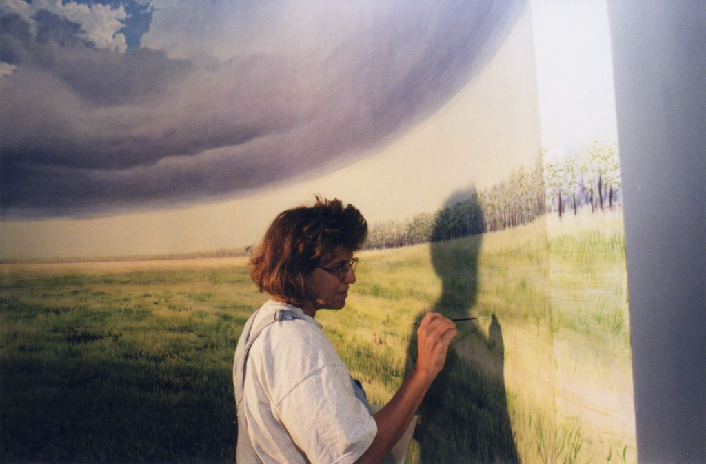 woman painting mural of cloudy Florida prairie scene